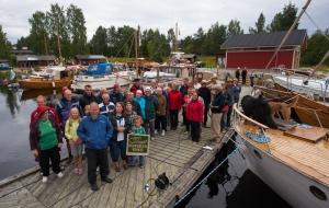 Osallistujajoukko lähettää iloiset terveiset kaikille puuvene- ihmisille.